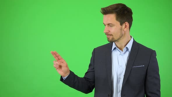 Thumbnail for A Young Handsome Businessman Smiles and Double Clicks at a Particular Spot - Green Screen Studio