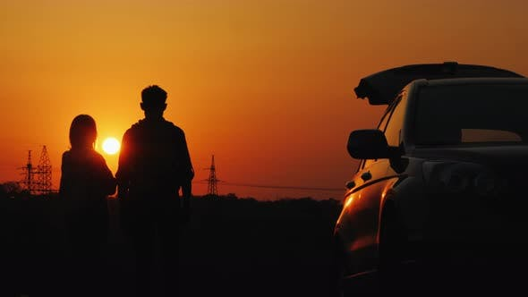 Thumbnail for A Young Couple Is Standing Near His Car and Admiring the Sunset Over the Guesthouse