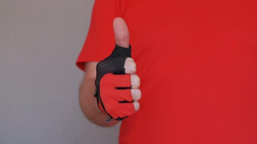 Sportsman Wearing a Red T-shirt and Sport Glove Raising a Thumb in Affirmation