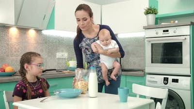 Mother with Baby Cooking Healthy Breakfast for Older Daughter