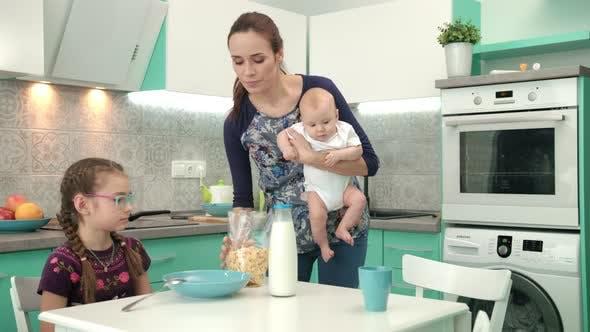 Thumbnail for Mutter mit Baby Kochen Gesundes Frühstück für ältere Tochter