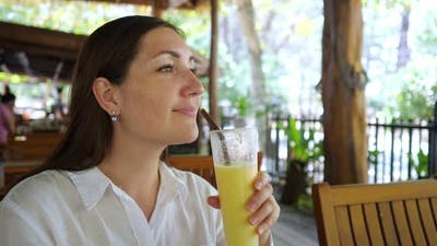 Woman in a White Shirt Drinks a Smoothie