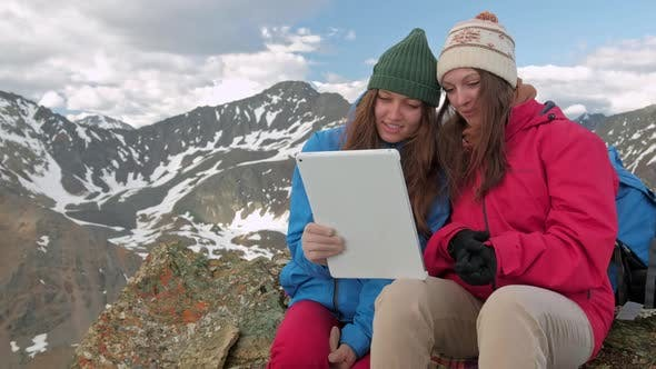 Thumbnail for Girls Hiker with a Tablet Sitting on a Rock on a Background of Mountains and Lakes, Norway