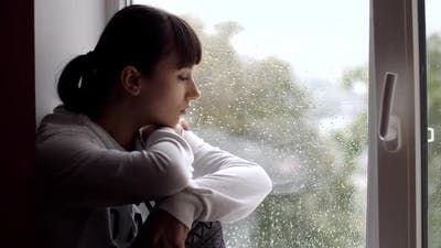 Sad Woman Sitting on Window
