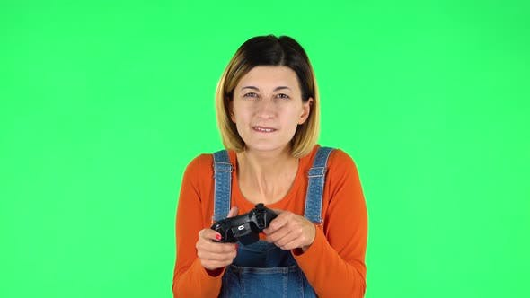 Cover Image for Girl Playing a Video Game Using a Wireless Controller with Joy and Wow Emotions. Green Screen