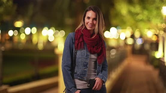 Thumbnail for Portrait of millennial girl in scarf and jean jacket, standing in park at night