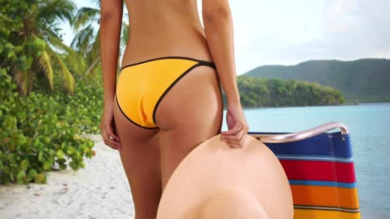 Thumbnail for Young white girl in yellow swimsuit standing next to a lounge chair holding  sun hat