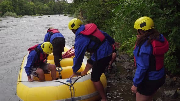Thumbnail for Group of people white water rafting getting into raft