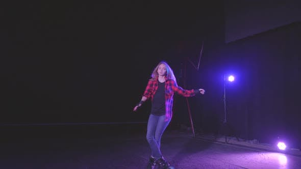 Active Young Attractive Girl on Roller Skates Professionally Spinning on Front Wheels in Dark Scene