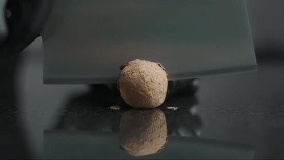 Thumbnail for Confectioner Cuts Chocolate Truffle By Knife on the Marble Table and Shows Truffle's Filling