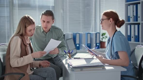 Man and Woman Get Poor Test Results During Medical Consultation with Female Therapist in Hospital