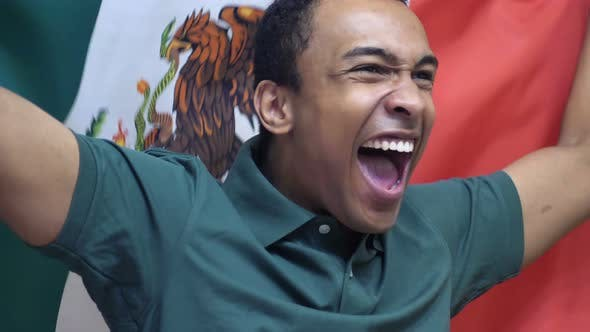 Thumbnail for Mexican Fan Celebrating while Holding the Flag of Mexico