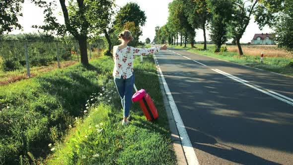Thumbnail for Traveler Girl Hitchhiking on a Sunny Road and Walking
