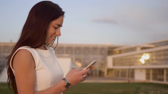Thumbnail for Seitenansicht des Lächelnden jungen SMS auf Smartphone Outdoor