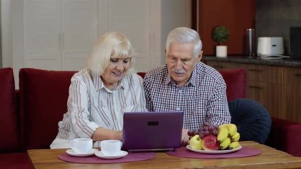 Senior Old Couple Grandparents Talking and Using Digital Laptop Computer at Home. Internet Shopping