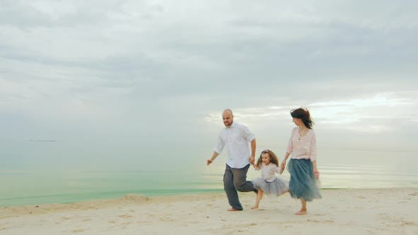 Cover Image for Happy Family of Three People Running on the Beach. Fun Games with Children