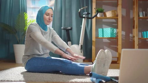 Beautiful Young Muslim Woman in a National Headscarf is Warming Up in Front of a Laptop