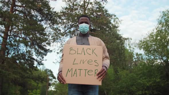 Thumbnail for African-American Man in Face Mask Protesting with BLM Sign