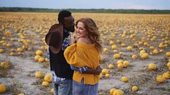 Couple Stands in Pumpkin Field and Hugs Rear View