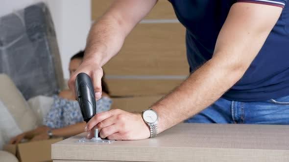 Thumbnail for Close Up Man Carefully Assembling Furniture