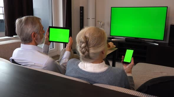 Thumbnail for Elderly Couple Sits in A Living Room, Watches Tv with A Green Screen, Looks at Smartphone and Tablet