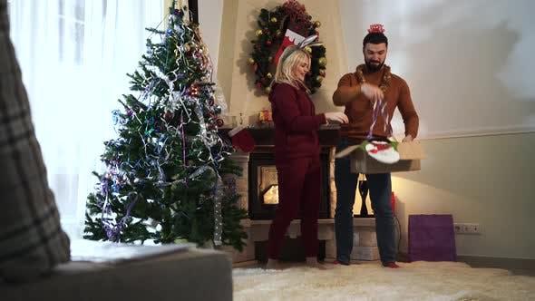Thumbnail for Freudige kaukasische Mann und Frau, die Spaß zu Hause am Silvester haben. Mann und Frau hängen