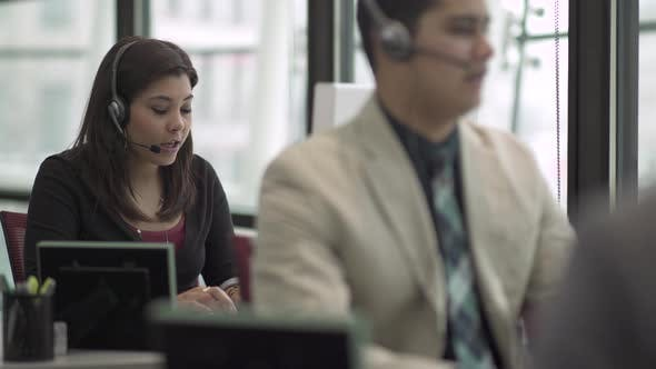 Thumbnail for Eine gemischte Rasse Frau arbeitet in einem attraktiven modernen Call Center (3 von 6)