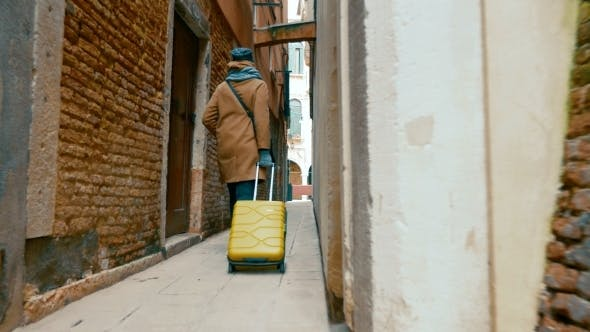 Thumbnail for Woman With Trolley Back Walking Along The Alleyway