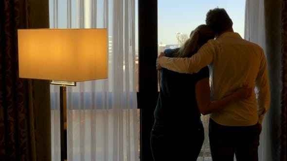 Thumbnail for Young Couple Hugging And Looking Out The Window