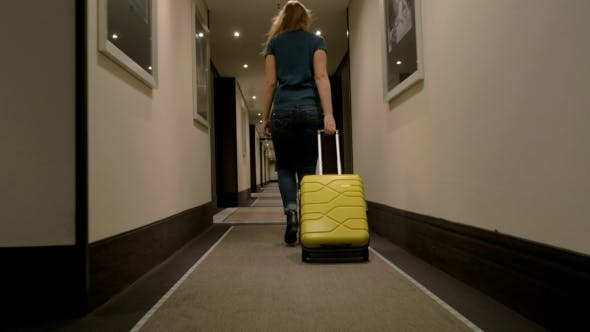 Thumbnail for Woman With Suitcase Walking In Hotel Corridor
