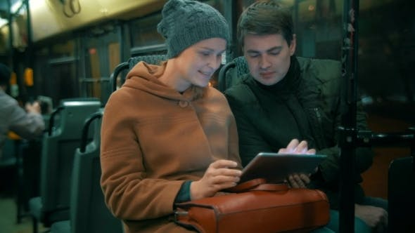 Young People Using Tablet Computer In The Bus