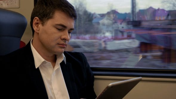 Thumbnail for Young Businessman Working With Pad In The Train