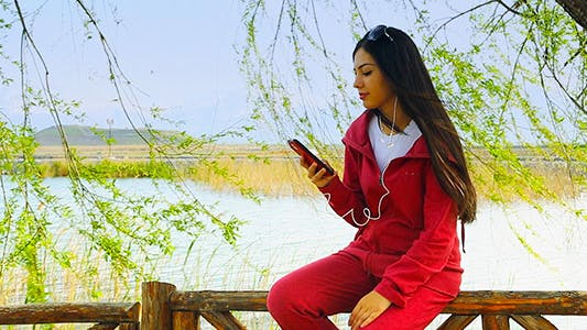 Thumbnail for Girl Listening to Music on a Smartphone