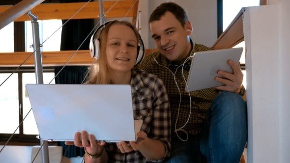 Cover Image for Young Couple In Heaphones At Home Enjoying Music
