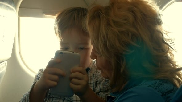 Thumbnail for Child And Grandmother Entertaining With Phone In