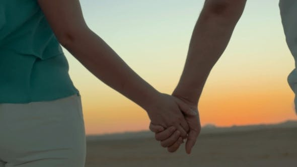 Thumbnail for Man And Woman Take Hands On The Beach
