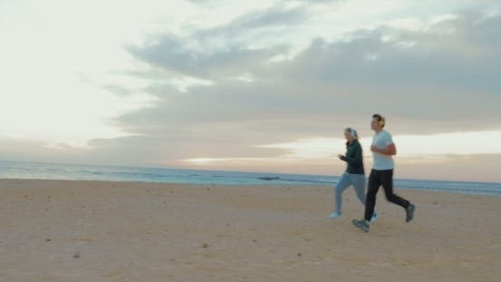 Thumbnail for Young Couple In Headphones Running On The Beach