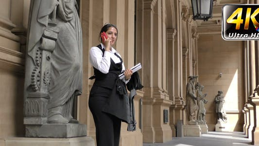 Business Woman Talking to Cellphone and Statues