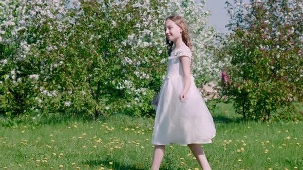 Entzückende Glückliche Teen Mädchen Gehen In der Nähe Blühende Bäume im Garten