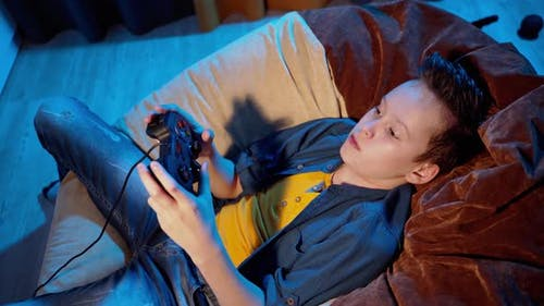 Young gamer playing video games at home