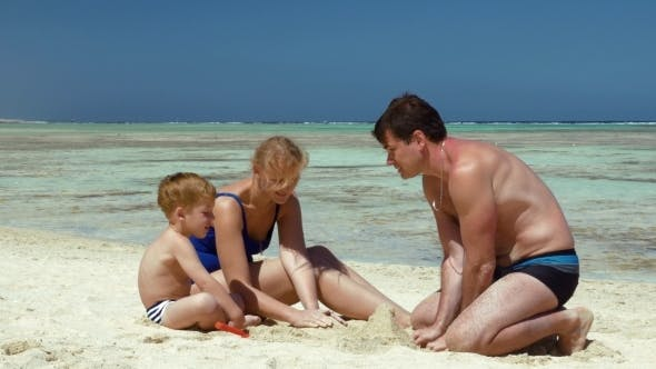 Thumbnail for Young Family Building Sand Castle
