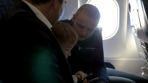 Thumbnail for Child And Young Parents Traveling By Plane