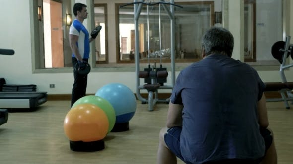 Thumbnail for Man Exercising With Weight Disks, His Friend