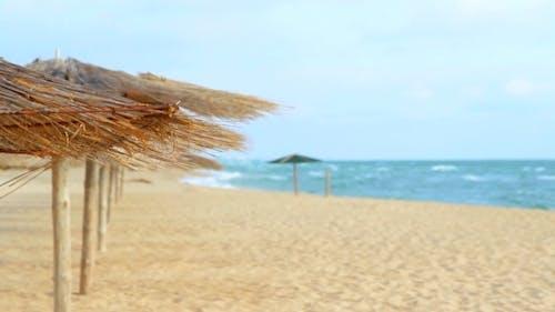 Straw Umbrellas On The Coast Of The Blue Sea.