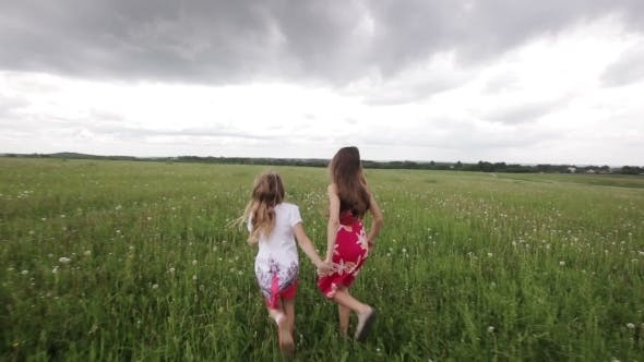 Thumbnail for Young Girl Running In a Field Holding Hands