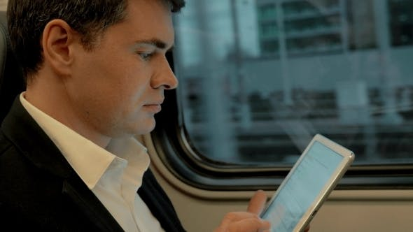 Thumbnail for Young Businessman Chatting On Pad In The Train