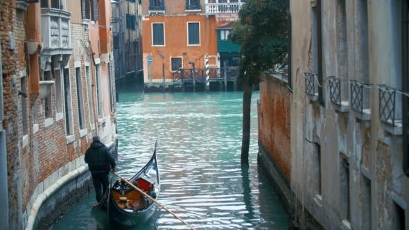 Veteran Gondolier Rowing Gondola Along Water Canal
