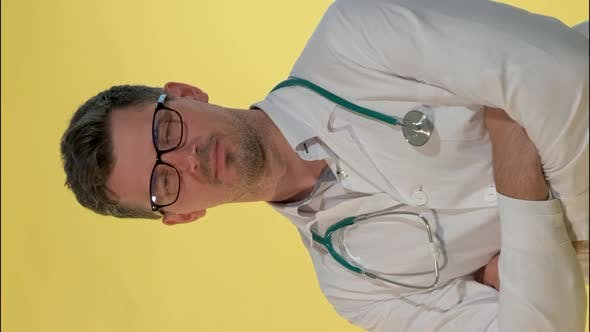 Handsome Doctor in Lab Coat Smiling To the Camera on Yellow Background.