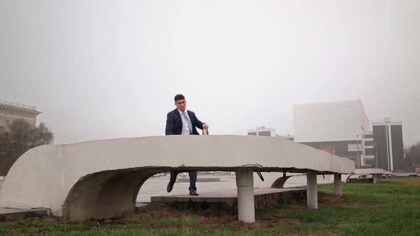 Successful Businessman in Suit Rush To Work and Jumps Over an Obstacle. Parkour