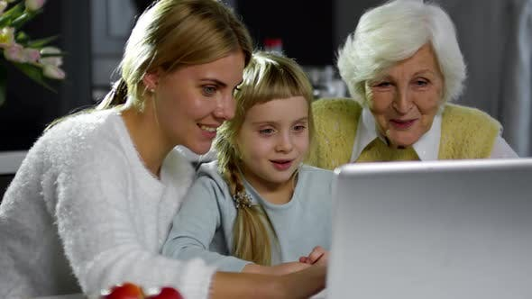 Cover Image for Little Girl Watching Cartoon on Laptop with Mom and Grandma